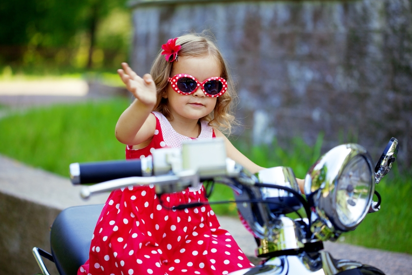 Beautiful little girl in a red dress on a motorcycle